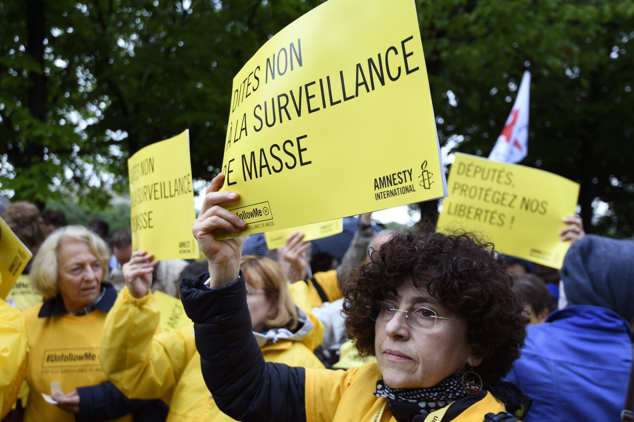 "Protesters holding placards reading ""Say no to mass surveillance"" take part on May 4, 2015 in Paris in a demonstration against the government's controversial bill giving spies sweeping new surveillance powers, deemed ""heavily intrusive"" by critics. AFP PHOTO / ALAIN JOCARD (Photo credit should read ALAIN JOCARD/AFP/Getty Images)"