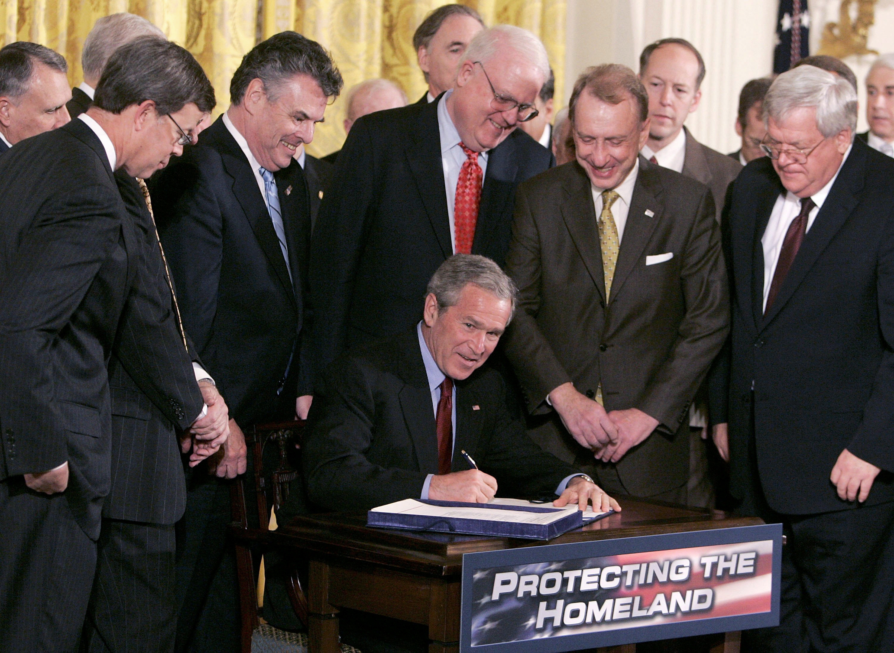 WASHINGTON - MARCH 09: Surrounded by members of Congress and Cabinet members U.S. President George W. Bush signs the H.R. 3199, USA PATRIOT and Terrorism Prevention Reauthorization Act of 2005 in the East Room at the White House March 8, 2006 in Washington DC. The reauthorization of the Patriot Act had come under criticism from some in Congress for the potential to infringe of civil liberties but was pushed by the Bush administration as essential for fighting terrorism. (Photo by Mark Wilson/Getty Images)